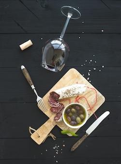 ワイン前菜セット。赤ワイン、フレンチソーセージ、黒の木製の背景にオリーブのガラス