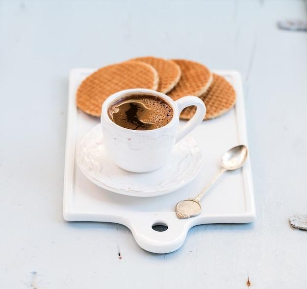 オランダのキャラメルストロープワッフルと白いセラミックサービングボードにライトブルーの木製の背景にブラックコーヒーのカップ
