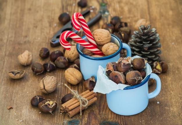 伝統的なクリスマス料理と装飾。ロースト栗のエナメルマグカップ、クルミ、シナモンスティック、キャンディー、素朴な木製のテーブルの松ぼっくり
