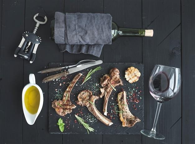 ラムチョップのグリル。ラムのラック、ニンニク、ローズマリー、スレートトレイのスパイス、ワイングラス、ソーサーのオイル、コルクのねじ込み機、黒い木製テーブルの上のボトル
