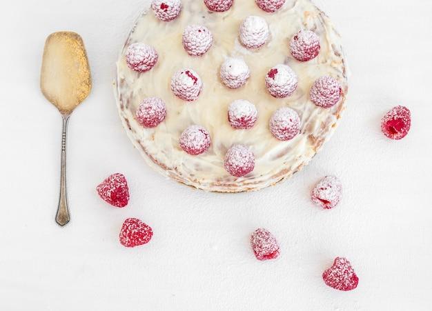白いテーブルの上のラズベリーケーキ