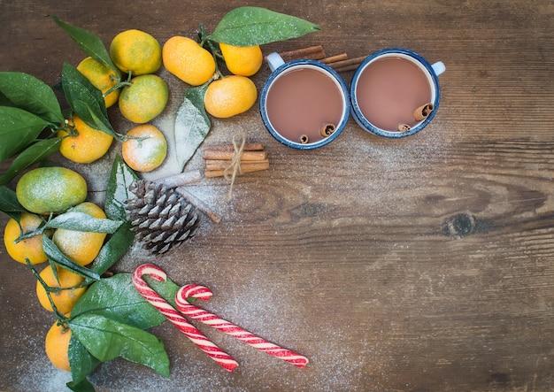 クリスマスまたは新年のフレーム。素朴な木製の背景、トップビューで葉、シナモンスティック、松ぼっくり、マグカップやキャンディー杖でホットチョコレートと新鮮なみかん