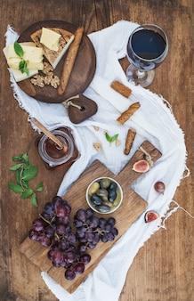 Стакан красного вина, сырная доска, виноград, грецкие орехи, оливки, мед и хлебные палочки на деревенский деревянный стол