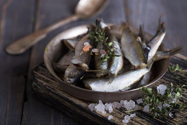 ワカサギ、イワシ、アンチョビ、新鮮なホウレンソウ、レモンスライス、マメ科植物などの正しい健康的な自然栄養の概念のための新鮮な海の冷水小魚。上面図