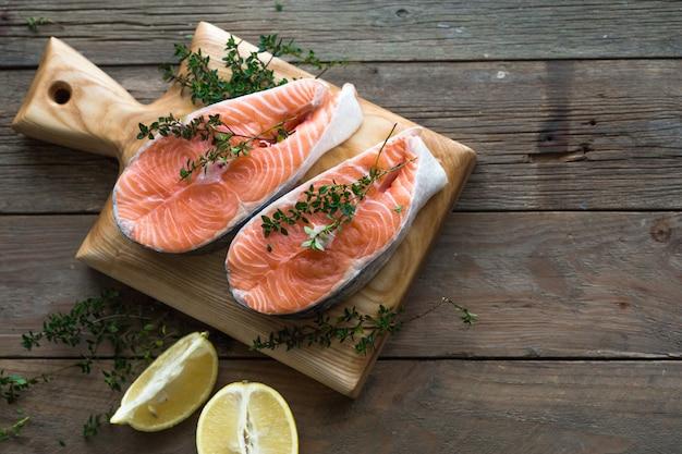 Сырой, свежий стейк из лосося на деревянной доске и специи вокруг. сырой лосось красная рыба. приготовление лосося, морепродуктов. концепция здорового питания. лосось и специи