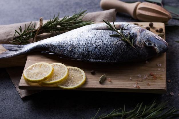 調理用食材と灰色の石のテーブルにまな板の上の新鮮な魚ドラド。コピースペースのトップビュー。