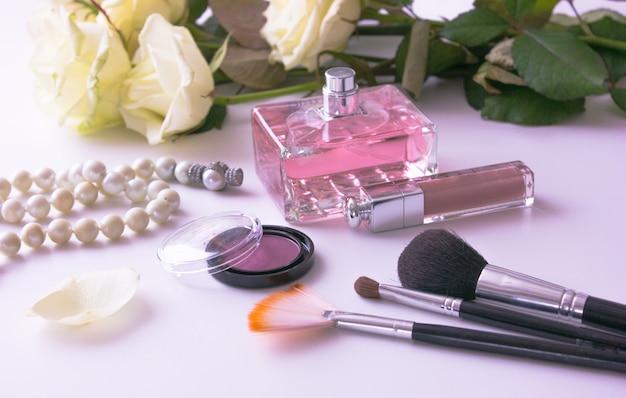 白のファッション女性オブジェクトの静物。女性のメイクアップのコンセプト。白いバラ、ピンクの香水と影、口紅、真珠