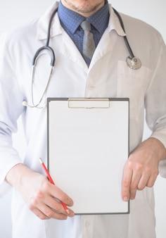 Доктор человек, показывая пустой буфер обмена знак на белом фоне. многорасовый медицинский работник.