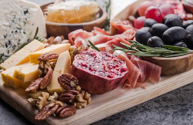 伝統的なイタリアの前菜プレート。木製のまな板にチーズの盛り合わせ。ブリーチーズ、チェダースライス、ゴゴンゾーラ、クルミブドウ、オリーブ、プロシュート、ローズマリー、赤ワインのグラス。上面図