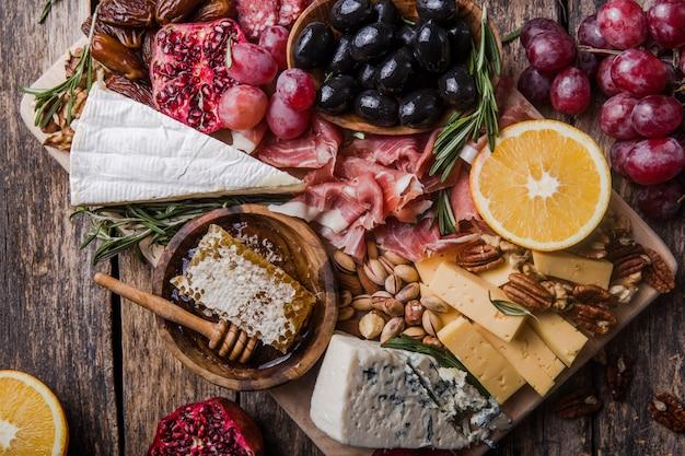 Традиционное итальянское блюдо с антипасто. ассорти сыров на деревянной разделочной доске. сыр бри, кусочки чеддера, гогонзола, виноград грецких орехов, оливки, прошутто, розмарин и бокал красного вина. вид сверху