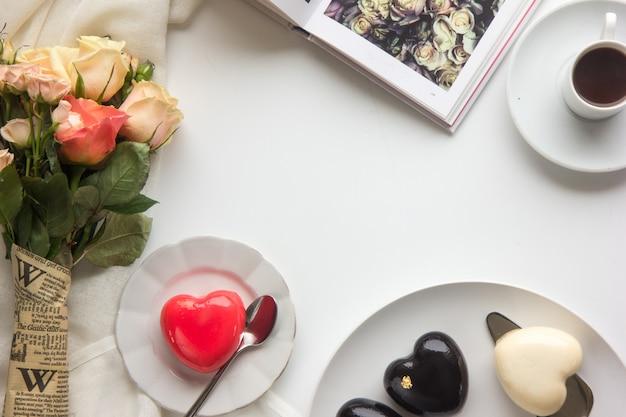木製の素朴な背景にミニハートで飾られたハートの形をしたピンクのムースケーキ。バレンタインデーや母の日のハート型のケーキ。上面図。平置き
