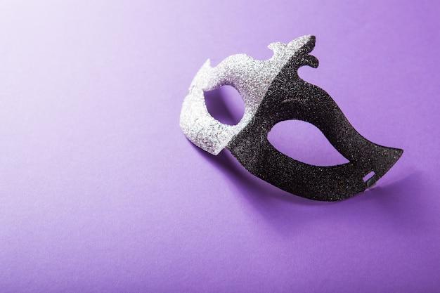 紫色の背景にお祝いのカラフルなマルディグラまたはカーニバルマスクのグループ。ベネチアンマスク。