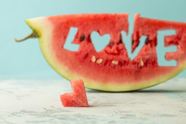 スイカの世界の愛、青いコピースペースに対する心のスライス。ハートの形をした穴のあるスイカ。夏、スイカの恋人、夏の販売コンセプト。