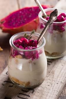 熟したドラゴンフルーツ、ピタヤまたはピタハヤの木製の背景、フルーツの健康概念に分離された自家製ヨーグルト