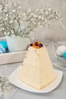 Традиционный русский пасхальный творожный десерт, православная пасха на сером бетонном столе с куличем, торты, цветы, крашеные яйца.