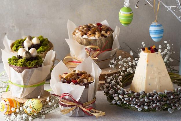 伝統的なロシアのイースターカッテージチーズデザート、正統派パスカクリーチケーキ、花、着色された卵と灰色のコンクリートテーブルの上。