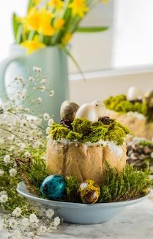 伝統的なロシアのイースターカッテージチーズデザート、正統派パスカクリーチケーキ、花、着色された卵とテーブルの上。