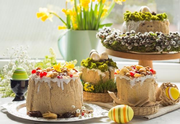Традиционный русский пасхальный творожный десерт, православная пасха на столе с куличем, торты, цветы, крашеные яйца.