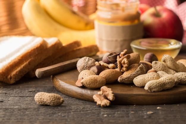 ナッツの品揃え。健康的な朝食の食材、フードフレーム。グラノーラ、ナッツ、フルーツ、ベリー、蜂蜜
