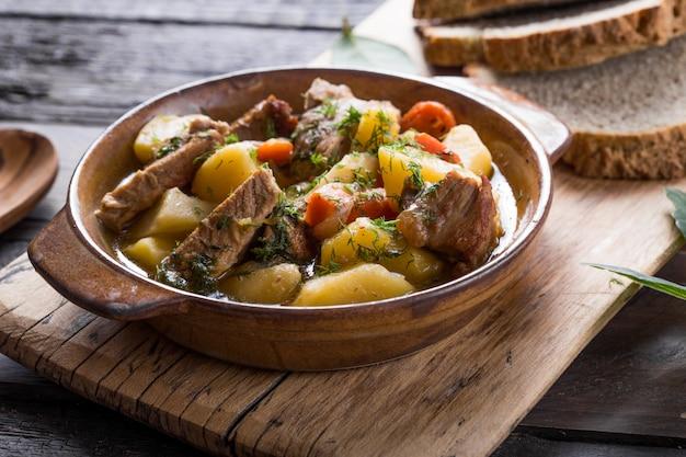 アイルランドの夕食。牛肉のポテト、ニンジン、ソーダパンの煮込み、木製のテーブル、平面図、コピースペース。自家製の冬の快適な食べ物-ゆっくり調理