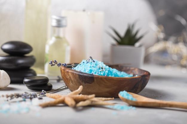Массажное масло флакон аромата эфирного и натурального аромата соли с камнями, свечи на бетонном сером столе.