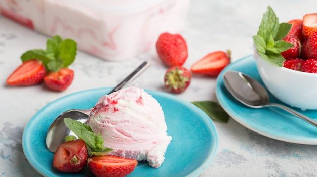 Вкусное клубничное мороженое черпает шарики на синюю тарелку с мятой.
