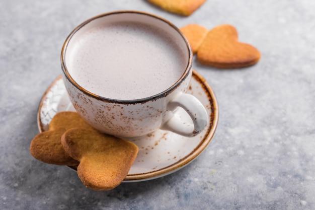 Чашка свежего кофе и сердечное печенье