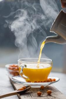 ウィンドウの前にガラスのカップで海クロウメモドキ茶。ハーブビタミン飲料