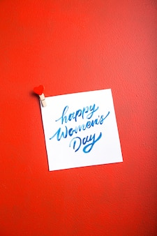 赤いテーブルに幸せな女性の日とカードメッセージ