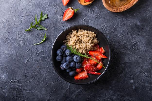 ブルーベリー、ストロベリー、蜂蜜、チアシードを含む健康的なビーガンダイエットサラダキノア。