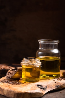 亜麻仁油と木製のテーブルに生の種子。