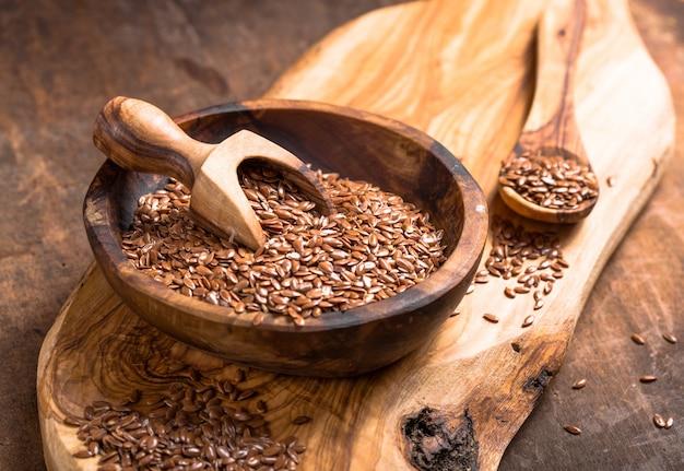 亜麻の種子または木製のテーブルの上にボウルのライン