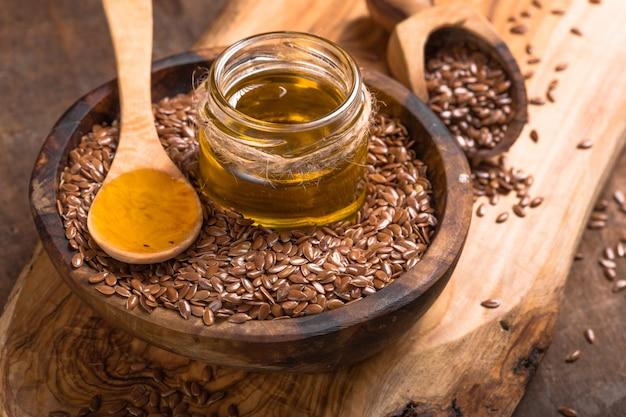 Семена льна масло и сырые семена на деревянный стол.