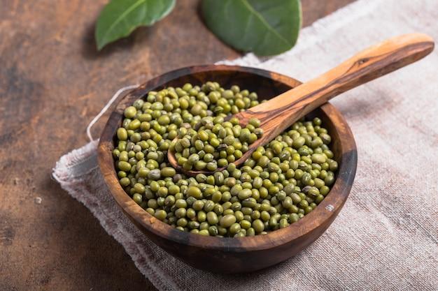 木製のテーブルの上にボウルに緑の豆
