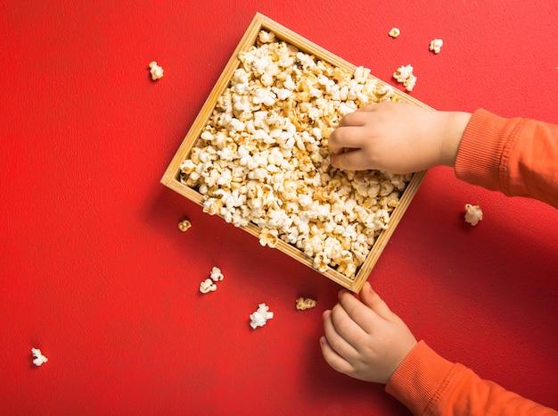 赤い背景の上から見たポップコーン。ポップコーンを食べる子。人間の手。シネマスナックコンセプト。映画やエンターテイメントを見るための食べ物。テキストのコピースペース、フラットレイアウト。