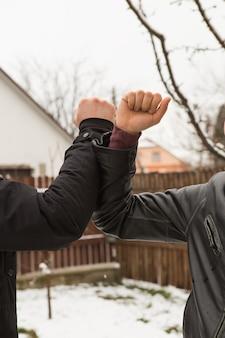 屋外で肘を振る友人。コロナウイルスを防ぐために新しいスタイルで一緒に挨拶する人々。握手をしないでください。肘の挨拶スタイル。