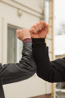 肘の隆起。友達が屋外で肘をぶつけています。コロナウイルスを防ぐために新しいスタイルで一緒に挨拶する人々。握手をしないでください。肘の挨拶スタイル。