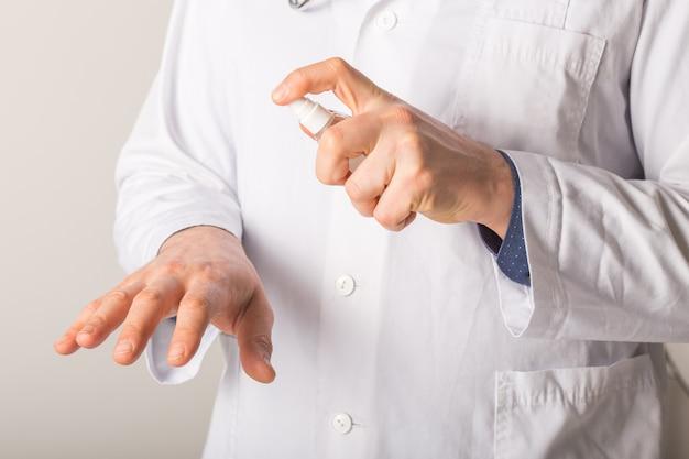 アルコール消毒剤で手を洗って医師の手。コロナウイルス危機でウイルス感染から身を守る