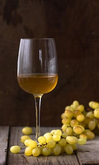 Стакан белого вина в винном погребе. старое белое вино на дереве.