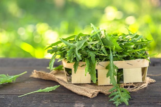 木製のボウルに新鮮な緑のルッコラの葉、白い木製の素朴な背景平面図のテキスト用のルッコラサラダ。ロケットサラダやルッコラ、健康食品、ダイエット。栄養の概念。