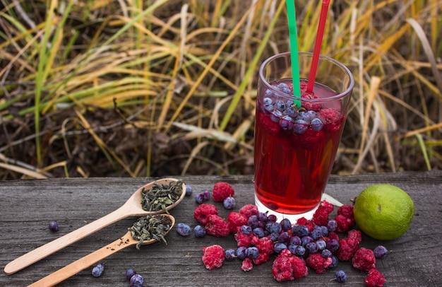 ベリーと木製のテーブルのガラスの果物からお茶。収穫、秋、秋、冬の温かいお茶、免疫飲料。