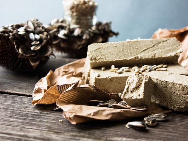 Халва. халва подсолнечника с семенами на деревянных фоне. праздничный восточный деликатес