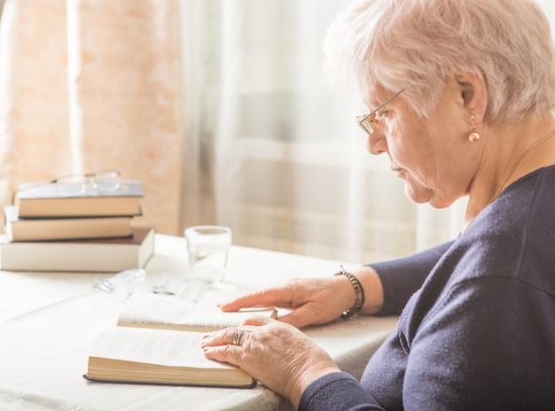 Пожилая женщина кавказа читает книгу. пенсионер релаксации и мозга образования удовольствие концепции. закрыть