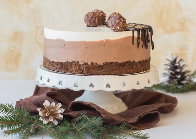 Цельный муссовый торт «три шоколада», посыпанный шоколадом, и украшенный конфетой