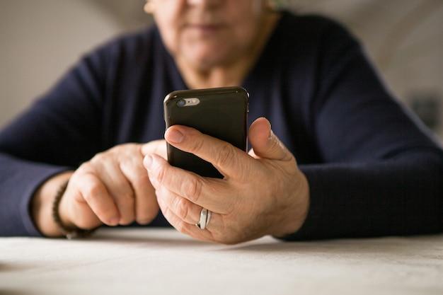 Пенсионерка пользуется мобильным телефоном на уютной домашней кухне. у бабушки перерыв на приготовление кофе