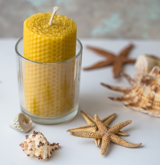 Восковая свеча с морскими звездами. натуральный воск. на светлом фоне.