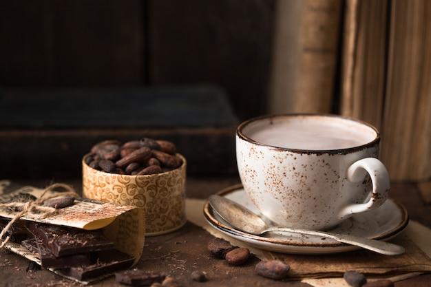 カカオ豆と古いテーブルに芳香族カカオのカップ