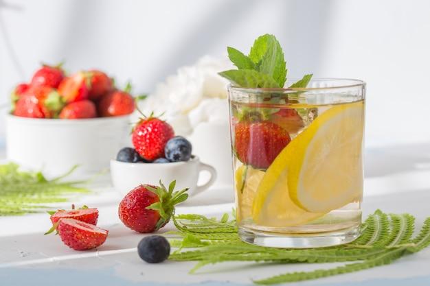 ガラスのレモネード。夏のさわやかなドリンク。レモンとベリーの冷たいデトックス水