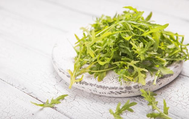 ホワイトボードに新鮮なルッコラの葉、テキストのための場所で素朴な木製の背景にルッコラロケットサラダ。セレクティブフォーカス、健康食品、ダイエット。栄養の概念