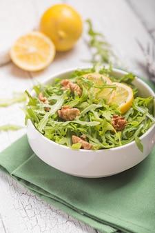 白いボウルに新鮮な緑のルッコラの葉、テキストのための場所で木製の素朴な背景にルッコラロケットサラダ。セレクティブフォーカス、健康食品、ダイエット。栄養の概念